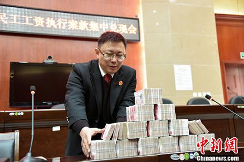 2016年1月份,北川法院为农民工讨薪,145万工资集中兑付,执法人员正在清点成捆的钞票。