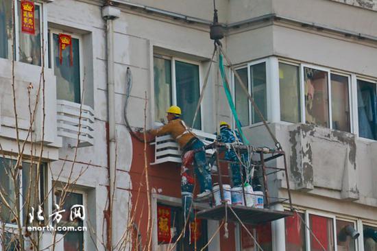 工人重新油漆建筑外墙