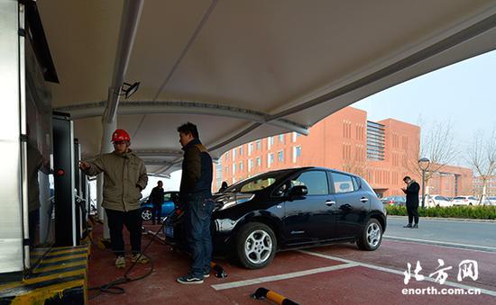 在南开大学电动汽车充电站,工作人员为市民讲解充电知识,为电动车进行充电。