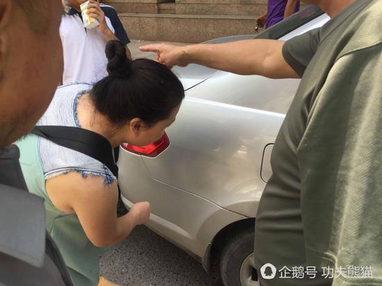 车主向家长指出车上的划痕。