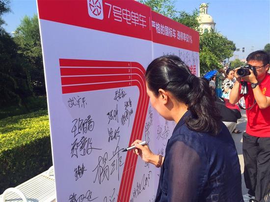 图片:南开区文明办主任路彤在7号电单车文明骑行宣传展台上签字