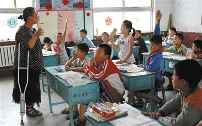 山东省枣庄市陶庄镇种庄中心小学教师孟凡芹在和孩子们做游戏。左腿被截肢的孟凡芹,单腿站立、跳跃上课已19年。图/视觉中国