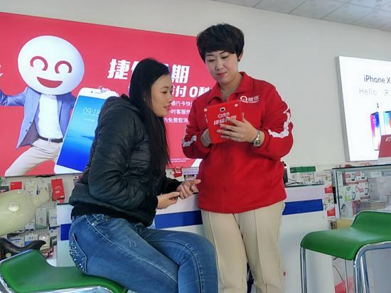 武清区手机店内消费者在捷信贷款服务点咨询办理事项