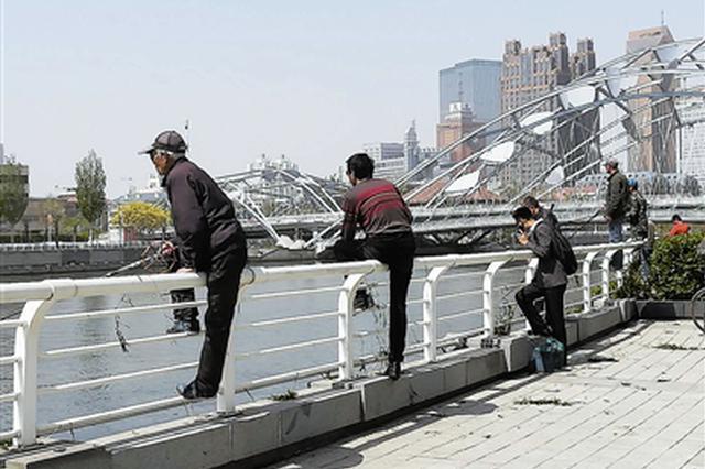 钓鱼市民跨护栏向河面倾斜 如此钓鱼看着就悬