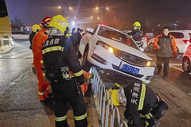 """小轿车欲""""跨""""栏 忙坏多位消防员"""