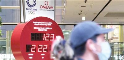 东京街头的行人戴着口罩经过显示东京奥运会倒计时的电子屏