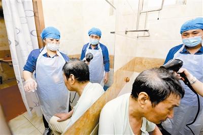 洗浴后工作人员帮老人吹干头发。