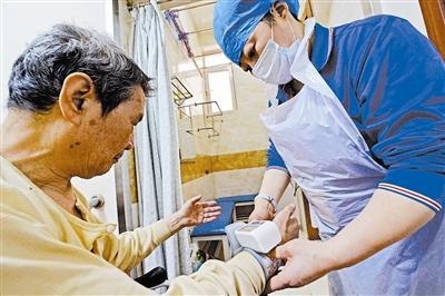 洗浴前工作人员为老人测血压。