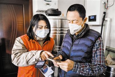 """图为工组人员向村民发放安全用电知识读本,讲解""""煤改电""""电价政策。"""