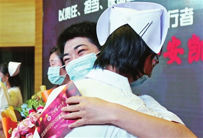 支援湖北医疗队护理工作者用大大的拥抱庆祝自己的节日。本报记者 谷岳 摄
