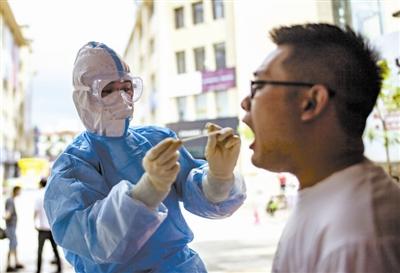 上图为医护人员为一名瑞丽市民进行核酸取样。