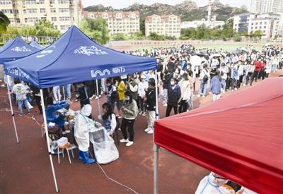 昨日,学生在青岛大学体育场检测点进行核酸检测采样。