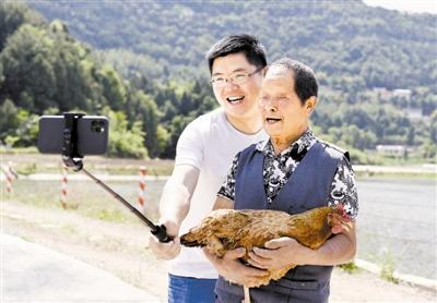 """5月13日,李君(左)与村民拍摄短视频,向网友介绍岫云村养殖的""""时光鸡""""。"""