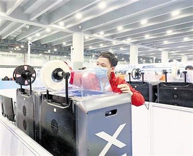 """昨天下午,参加""""制造团队挑战赛""""的天津选手李明楼正在进行3D打印设备调试。"""