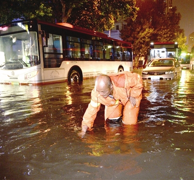 排水人员在荣业大街打井放水。 本报记者 张磊 摄