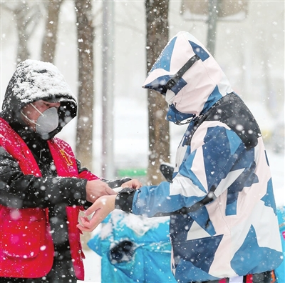 纪明家园社区的党员志愿者在大雪中对进入小区的居民测量体温。