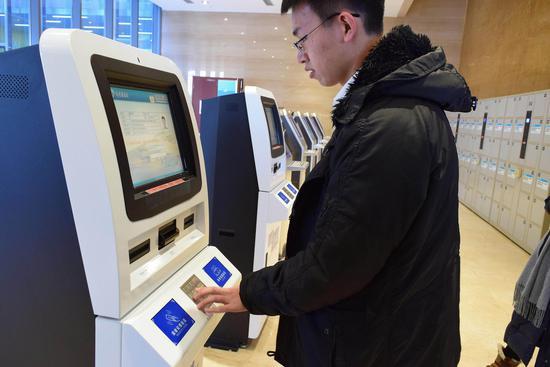 在武清图书馆内,市民利用自助办证机办理借阅证