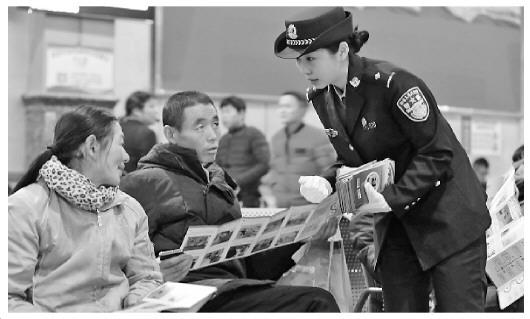图为警方在火车站向旅客宣讲春运安全注意事项。
