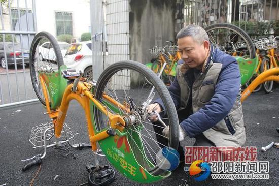 夏英雄正在给送来维修的自行车换胎。