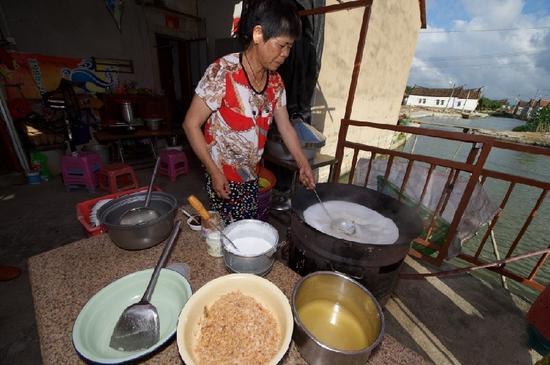 """5月27日,埭美村一位经营小吃店的村民在为游客做当地美食""""锅边糊"""""""