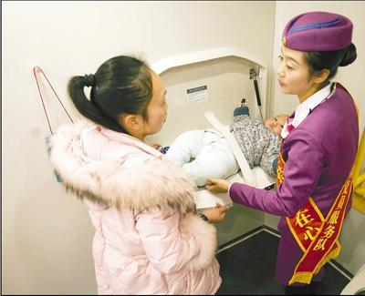 对于带婴儿乘坐高铁的妈妈来说,母婴室显得尤为必要。图为G82次高铁母婴室内,列车员正在协助一位年轻妈妈照护婴儿。彭 年摄
