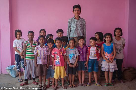 """卡兰和学校的同龄学生站在一起,看上去""""鹤立鸡群""""。(图片来源:英国媒体)"""