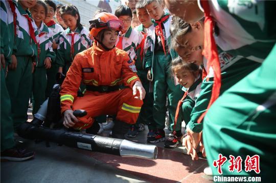 图为消防员耐心为孩子们讲解防火常识。 王博悟 摄