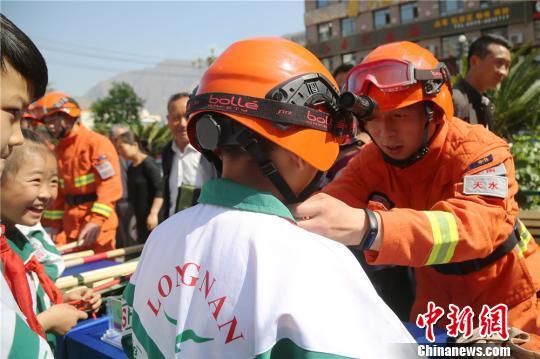 图为消防员为孩子们穿戴灭火头盔。 王博悟 摄