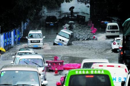 昨日,南岸盘龙立交桥,洪水淹没道路,车辆通行困难。