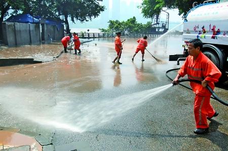 昨日,渝中区长滨路,环卫工人在清洗淤泥。