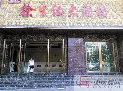 刘嘉抱着父亲遗像坐在事发酒店门口。