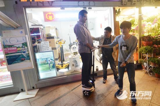 图为一位外籍顾客正在体验电动平衡车
