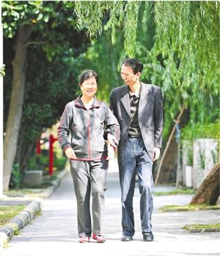 殷立明陪妻子在小区散步、锻炼身体。