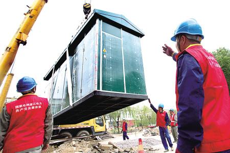 昨天,鄞州供电公司施工人员在鄞州金谷南路无轨电车充电站,把两台特制的箱式变电设备吊装到位。(胡建华 郑之超 摄)