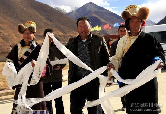 西藏墨竹工卡县的藏族村民手捧哈达欢迎游客(10月23日摄)。