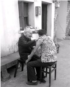 程奶奶在为邱小芬按摩胳膊。记者李竹青摄