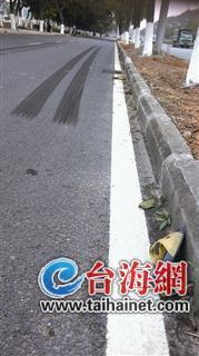 路上留下很长的刹车痕迹,路边落着被撞孩子的拖鞋
