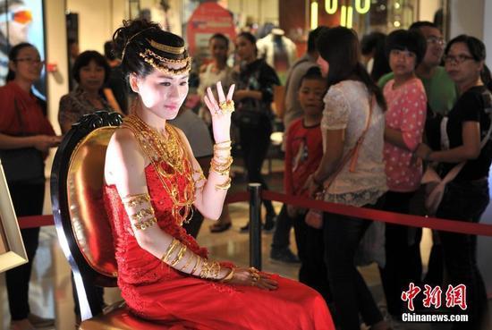 一浑身挂满黄金首饰的美女坐在福州商场内,吸引许多民众驻足观看。