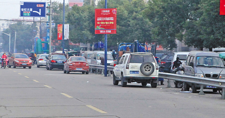 盛莫路菜场边,很多买菜车直接停在机动车道上,致使交通拥堵。