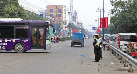 在协警的护卫下,公交车得以顺利从场站开出。(记者 余建文 摄)