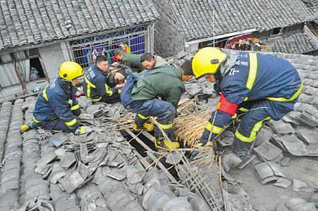 图为消防队员正在拆除屋顶瓦片,让老人平安降落。   (骆承 摄)