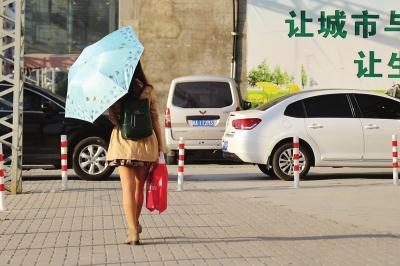 昨日气温较高,一位女士打着伞遮阳东快记者刘朔/图