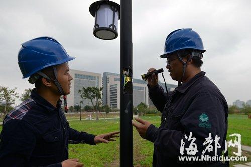 花海公园内,路灯杆电线裸露,电力技工(右)和海都记者一同排除隐患