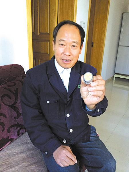 叶小华展示老人送给他的18枚纪念币。(王伊婧 摄)