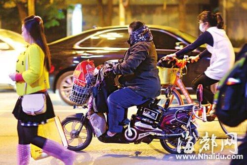 天气阴冷,电动车骑手将自己包裹得严严实实的