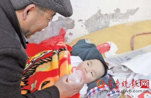 枣庄滕州殡葬师王师傅在出租屋内给一名五个月大的弃婴喂水。