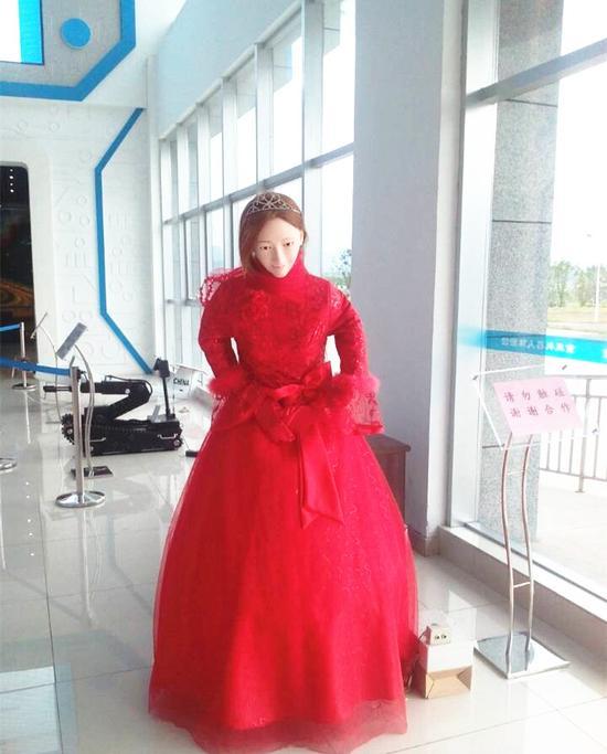 一个身穿红色礼服的仿真美女机器人向嘉宾问好