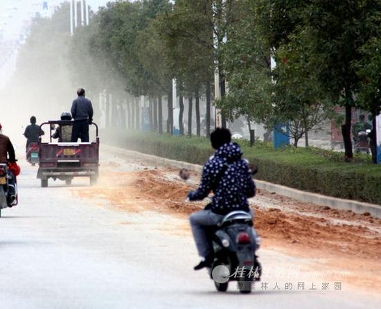 撒落在东二环路上的渣土被来往车辆不断碾压,大风一刮,灰尘四处飘散。记者邱浩 摄