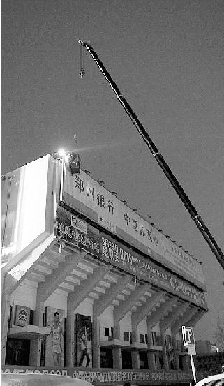 工作人员对市体育馆楼顶违法广告进行拆除。