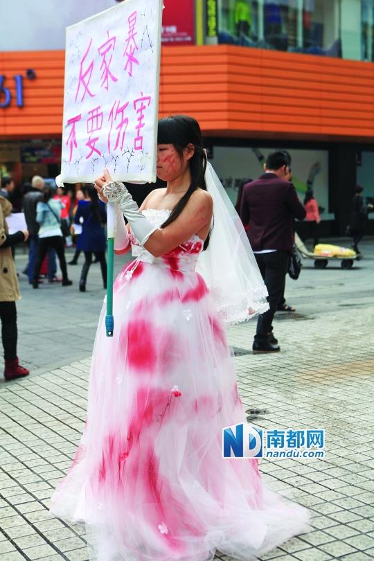一名女子穿着染红的婚纱,希望社会关注反对家庭暴力。南都记者 赵炎雄 摄